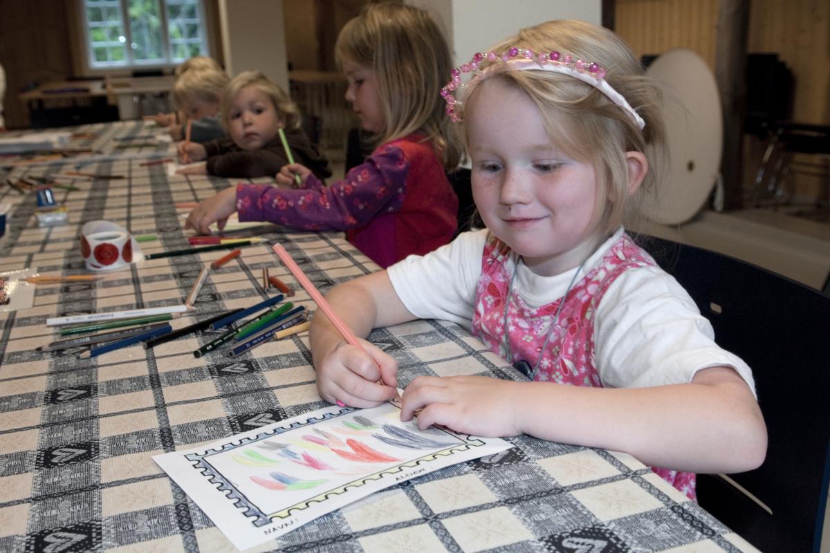 Jente sitter og tegner på Norges Postmuseum.