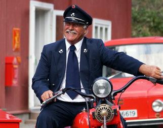 Postmann på historisk rød postmotorsykkel med sidevogn foran Postgården på Maihaugen.